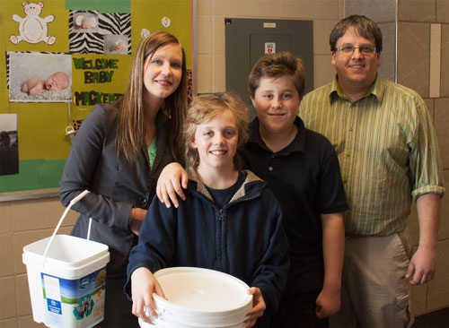 """St. Ann Catholic School """"Battery Lead"""" students Blain and Schuyler pose for a picture with Sarah Lacharity of Raw Materials Company and Mr. Kuczera of St. Ann Catholic School"""