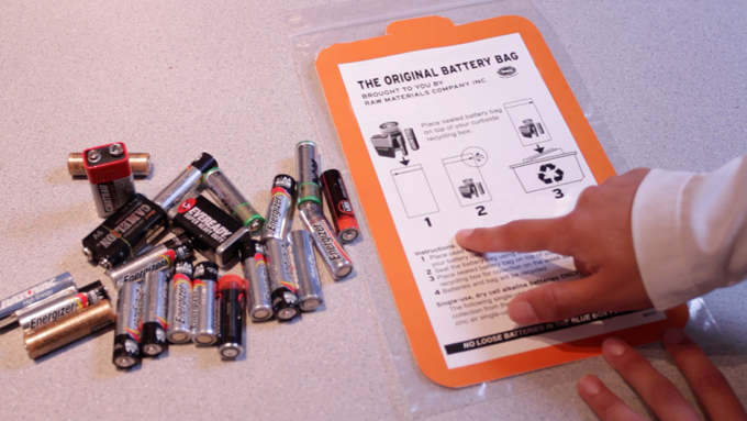 A picture of a resident reviewing the instructions on a battery recycling bag before rounding up their used batteries for a special curbside collection.