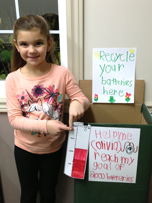 Olivia poses with her battery recycling container she made for the Ontario Schools Battery Recycling Challenge
