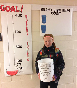 Grandview student stands beside the school's goal thermometer that keeps track of how many battery pails the school has recycled to date.